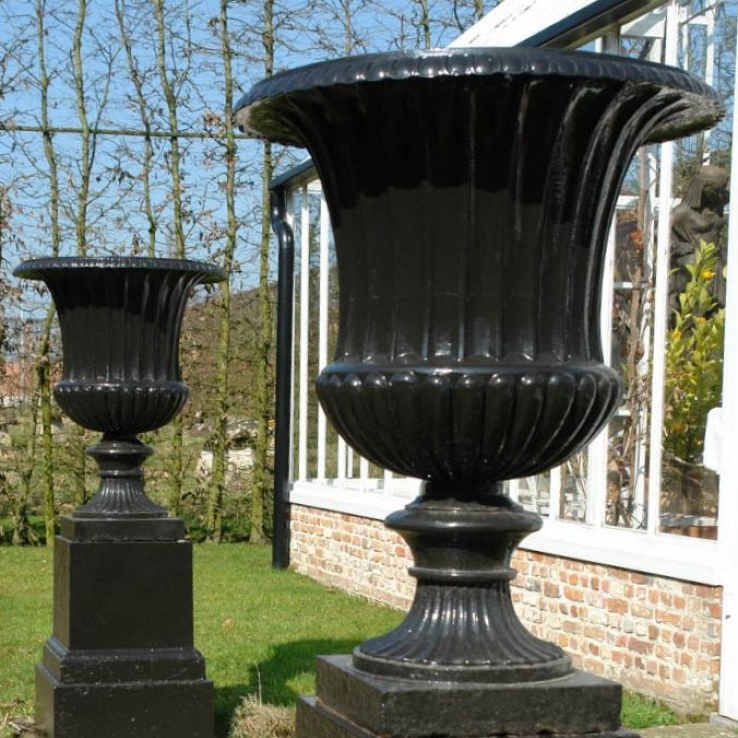 A pair of Handyside foundry cast iron garden urns on stands